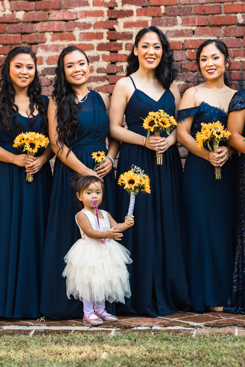 Bridesmaids in mismatched navy blue dresses with yellow sunflower bouquets