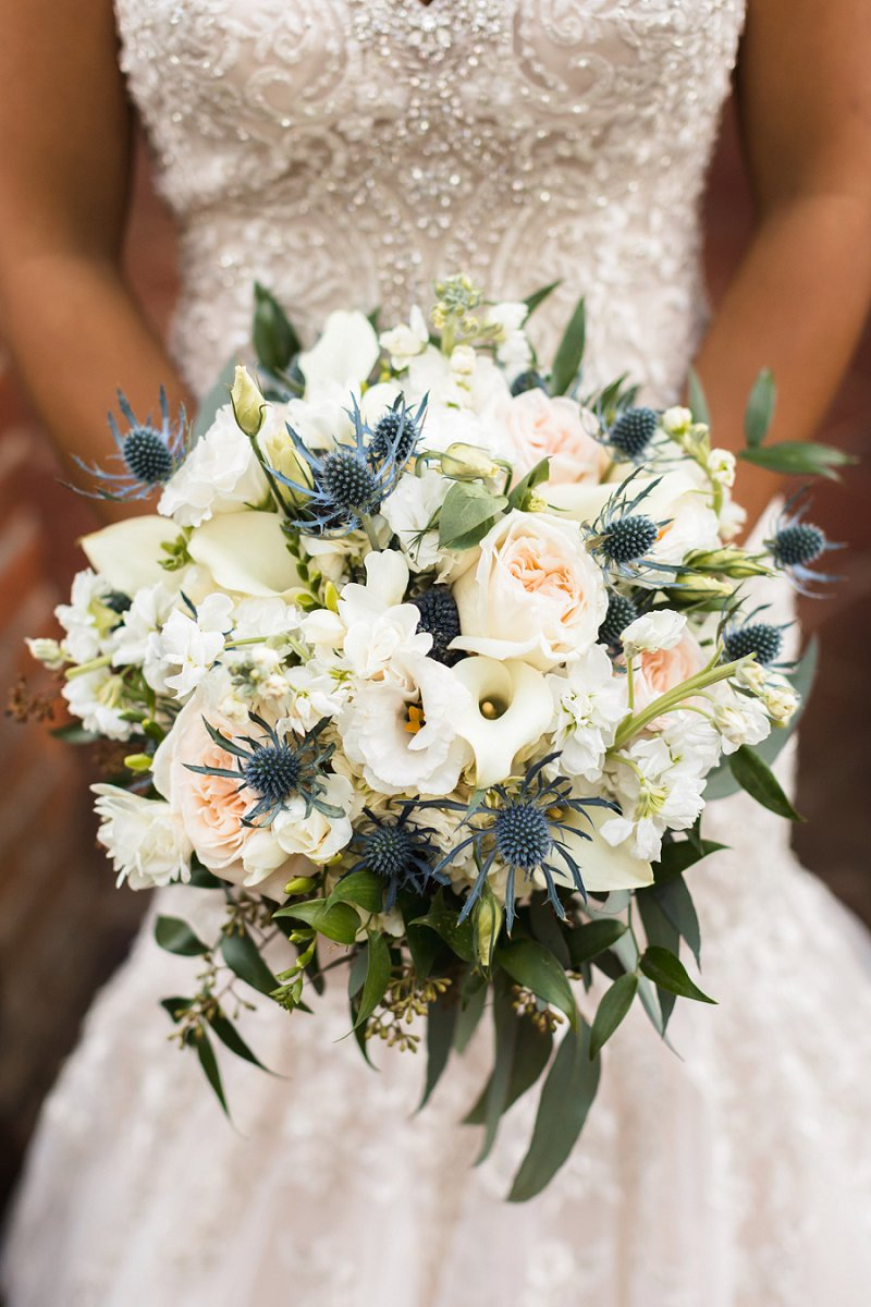 Round wedding bouquet with blue thistle and calla lilies