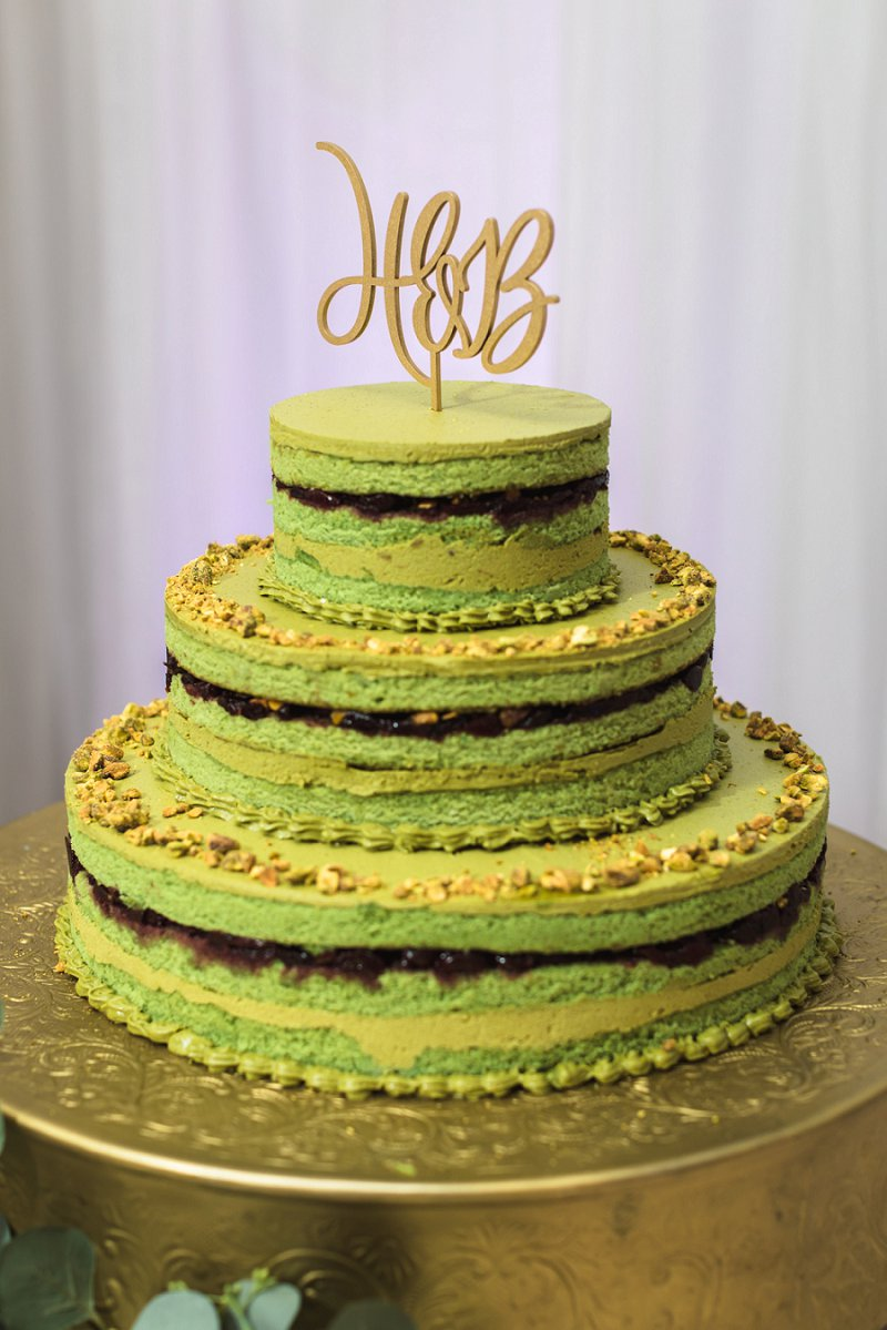 Delicious and unique green pistachio tiered wedding cake with cherry compote and monogram cake topper
