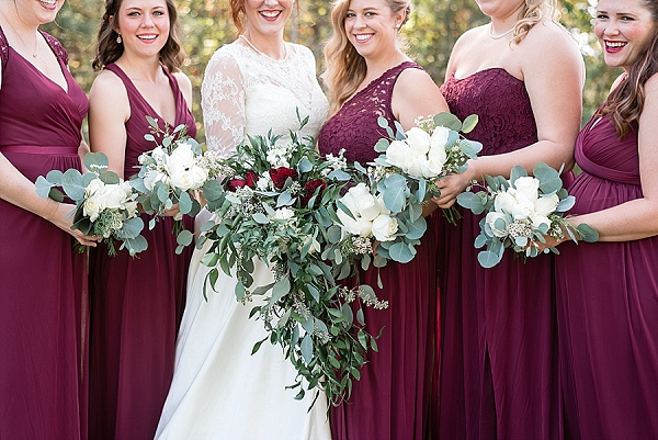 Burgundy red bridesmaid dresses and eucalyptus bouquets