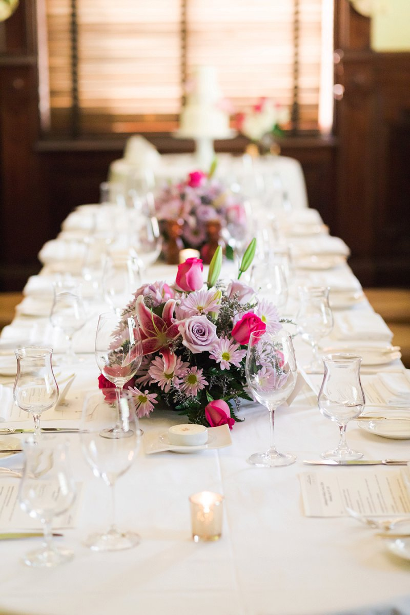 Cheerful and traditional wedding reception centerpiece with pink lilies and purple daisies
