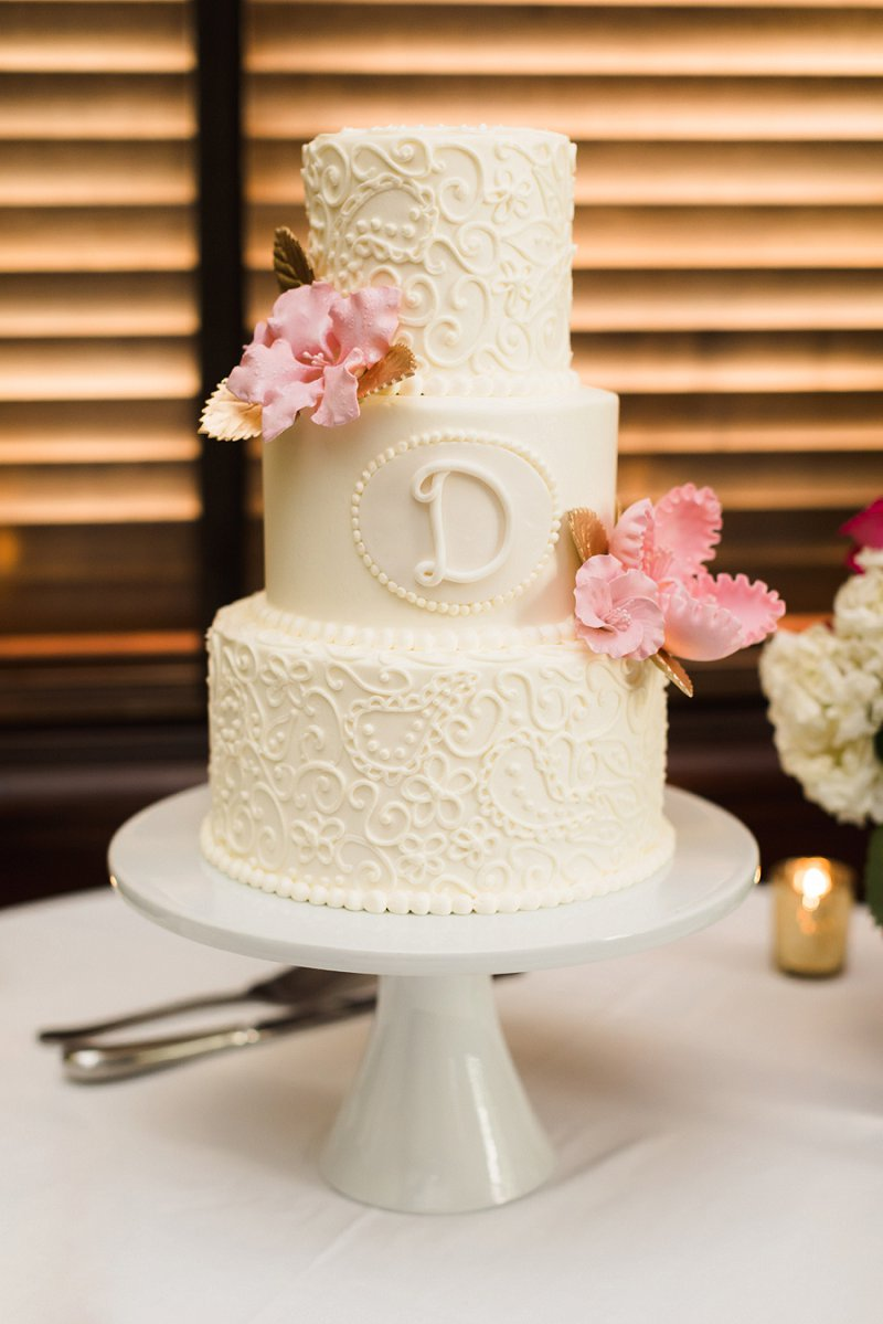 Classic white tiered wedding cake with paisley sugar art and pink sugar hibiscus flowers
