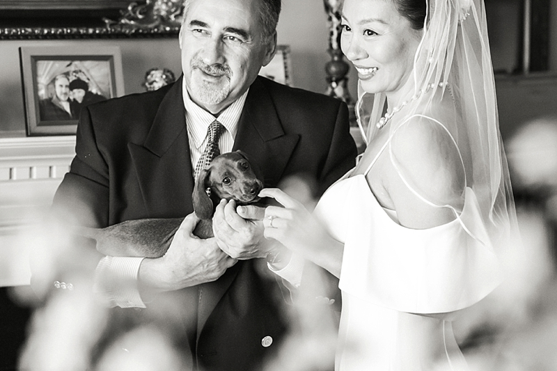 Sweet wedding moment between bride and groom with their dog