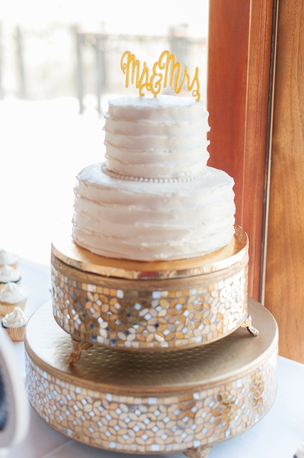Simple white two tiered wedding cake on gold mosaic cake stand