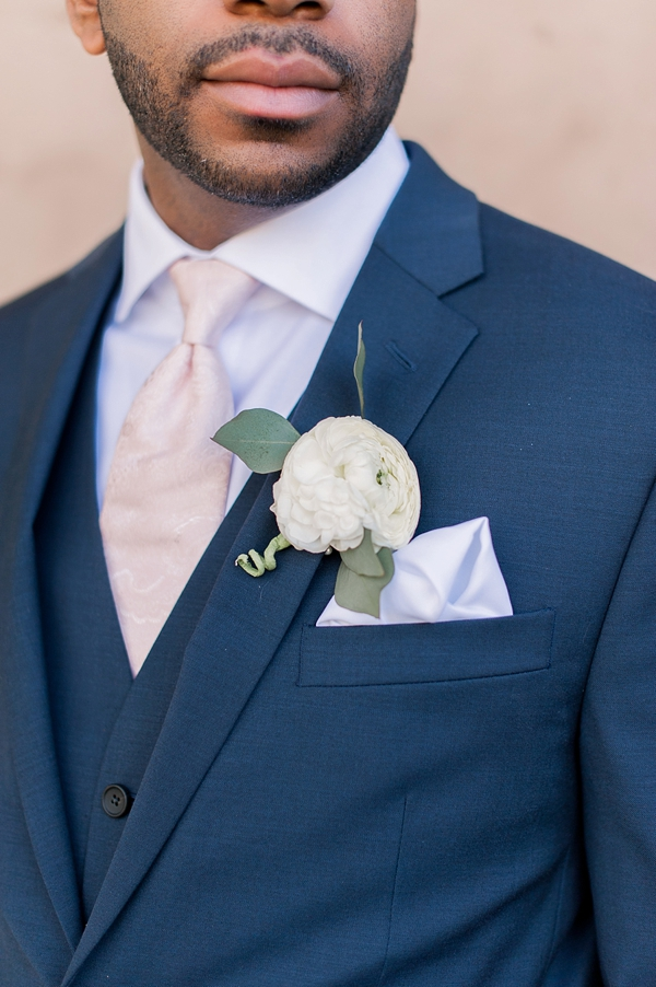 White boutonniere with ranunculus and eucalyptus