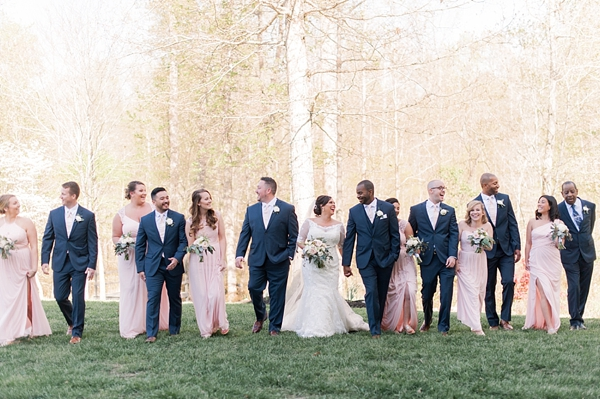 Wedding party in pink dresses and navy blue suits