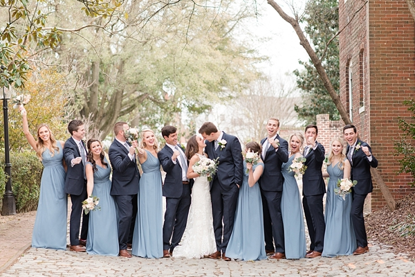 Wedding party in blue bridesmaid dresses and classic navy blue suits