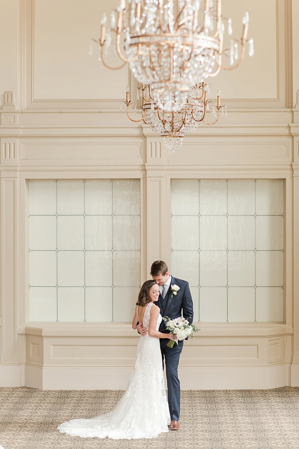 Classic ballroom wedding portrait of bride and groom with gold chandeliers