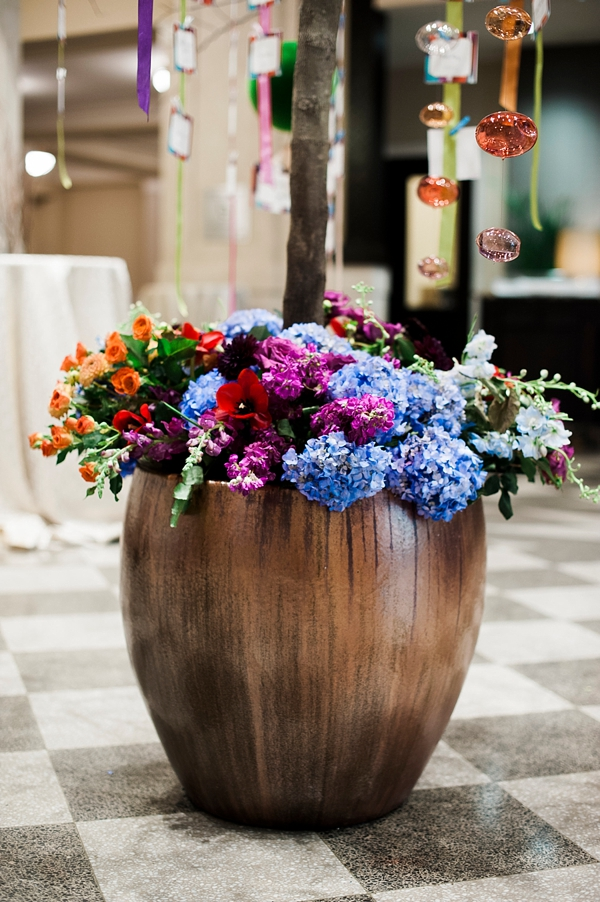 Colorful wedding flowers in giant flower pot for escort card display