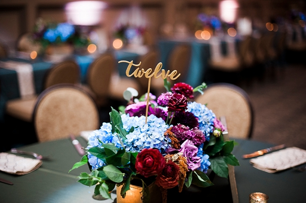 Gold written table number picks in wedding centerpiece