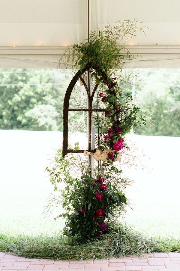 Beautiful wedding ceremony altar area with a wooden church window and florals and greenery