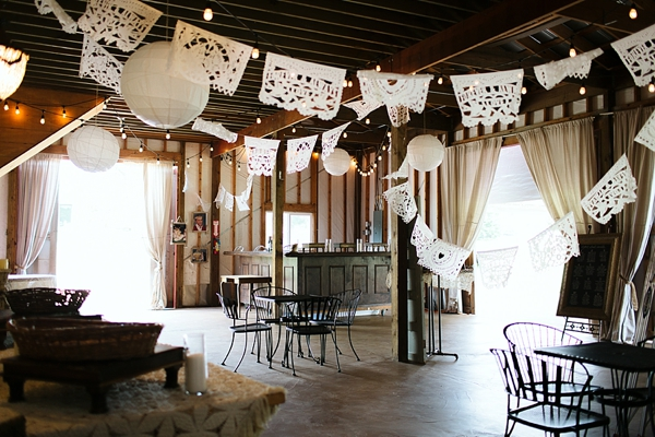 Handmade barn setup for cocktail hour with paper flags and paper lanterns hanging above
