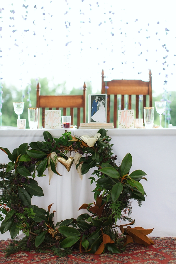 Eclectic sweetheart table with magnolia wreath and handmade Mr and Mrs signs