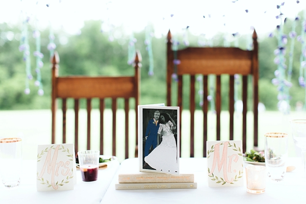 Wedding sweetheart table with fun photo of bride and groom wearing paper doll clothes