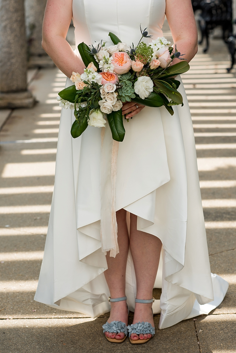 Garden inspired wedding bouquet with David Austin roses held by a bride wearing a high and low hem wedding dress
