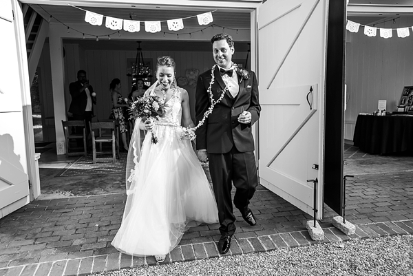 Beautiful bride and groom exiting ceremony with papel picado banner and wedding lazo