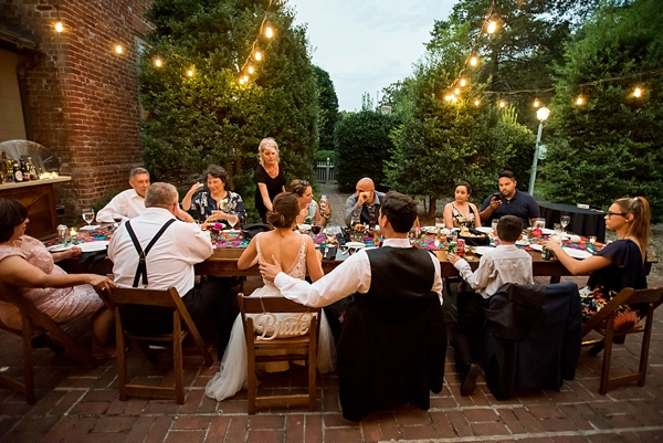 Intimate al fresco wedding reception with farm table and bistro lights