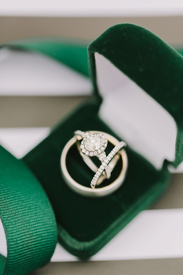 Emerald green velvet ring box with wedding rings