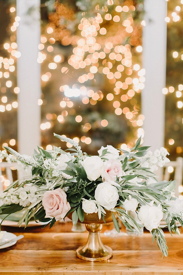 Low wedding centerpiece in gold vase and twinkle lights