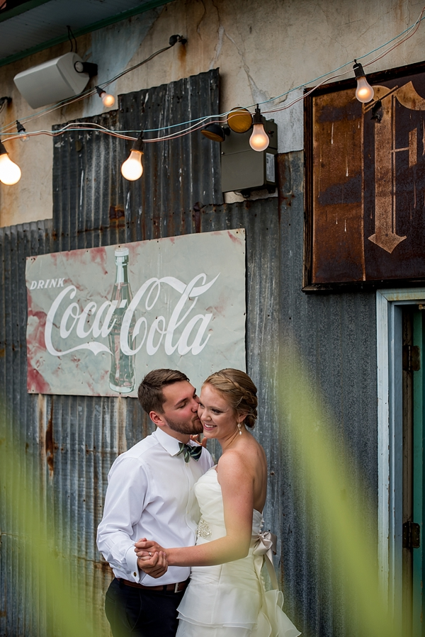 Adorable bride and groom in front of vintage industrial signs