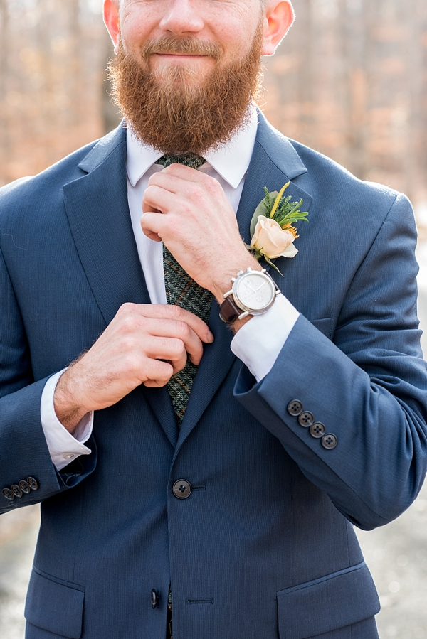 Stylish blue grooms suit and dark green necktie