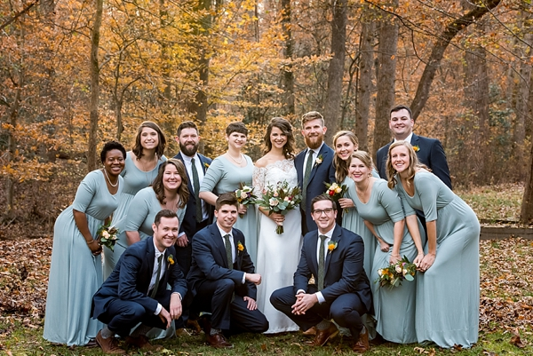 Beautiful wedding party with sage green bridesmaid jersey dresses and groomsmen in blue suits