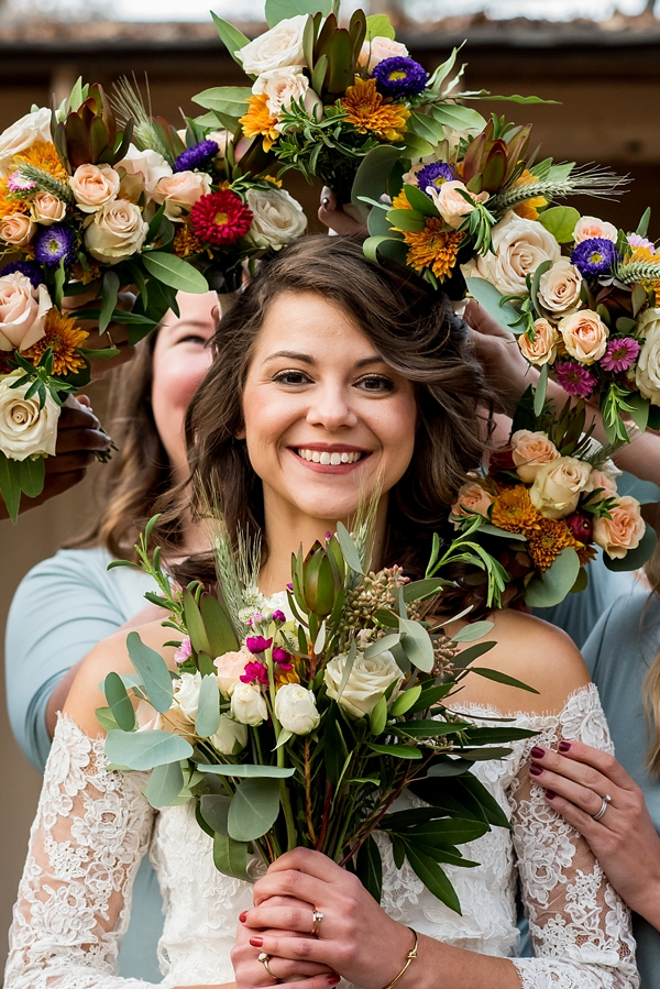 Fun wedding portrait idea with bride surrounded by her bridesmaids bouquets