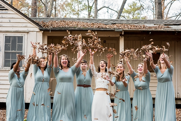 Bridesmaid and bride throwing fall leaves for fun wedding portrait idea