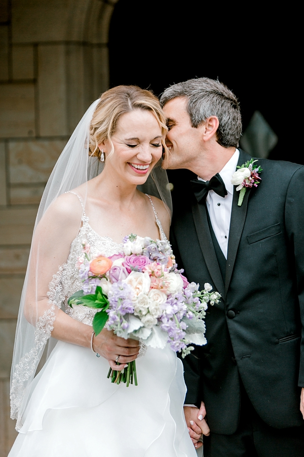Bride with pink and purple bouquet and happy groom