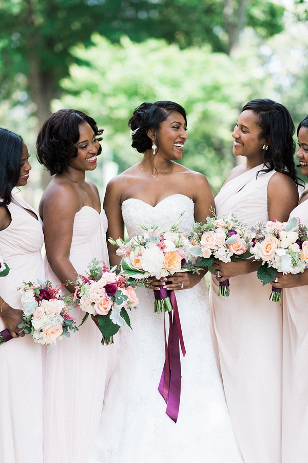 Bridesmaids in blush pink dresses holding burgundy red and peach bouquets