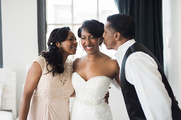 Brides parents kiss their daughter bride