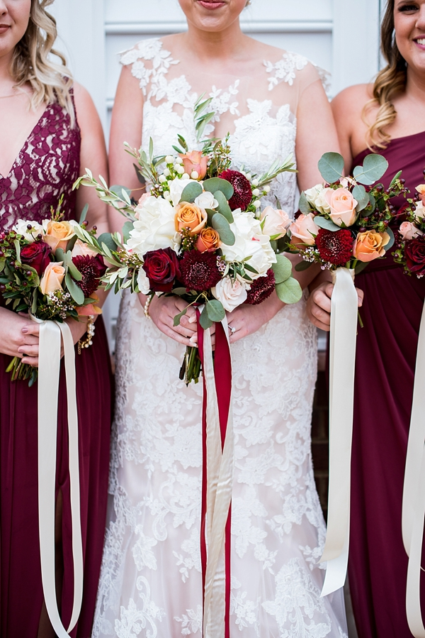 Burgundy red wedding bouquets with pops of burnt yellow and white