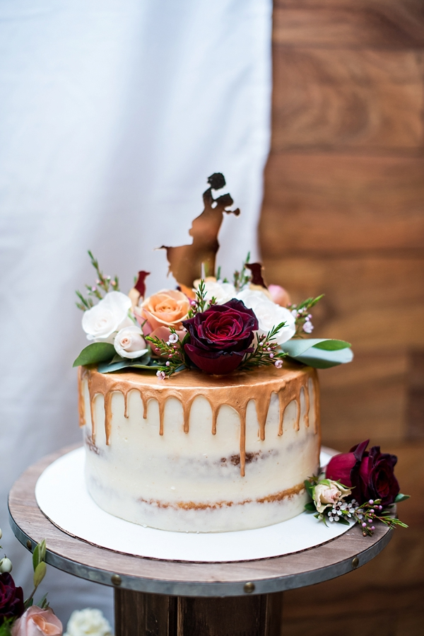 Semi naked wedding cake with gold copper drip and red flowers