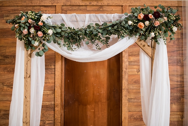 Wedding ceremony wooden arch with drapery and flowers