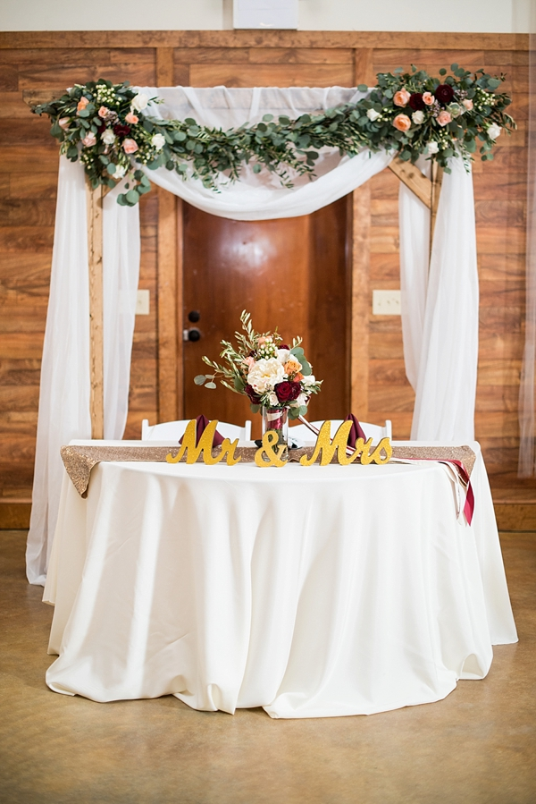 Rustic sweetheart table with wooden arch and floral swag backdrop