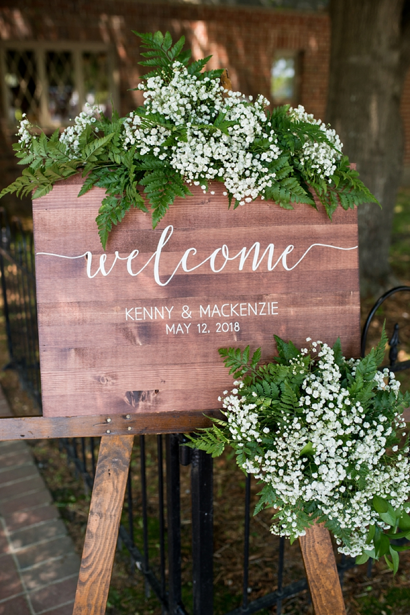 Wooden welcome wedding sign with babys breath and greenery swag for rustic winery ceremony