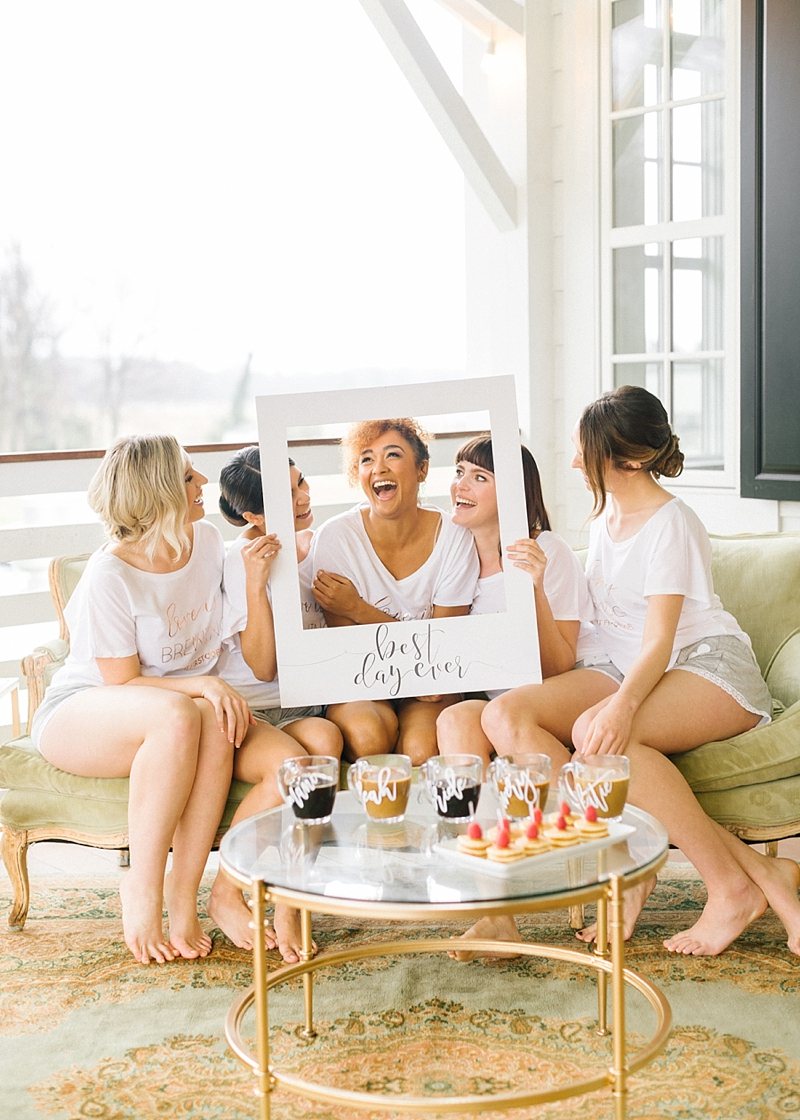Bride and her bridesmaids share a fun getting ready moment with giant Best Day Ever Polaroid sign from Davids Bridal