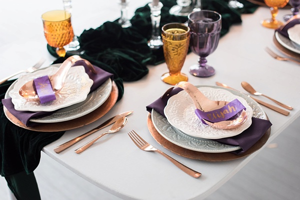 Purple and green sweetheart table with emerald velvet runner and copper flatware