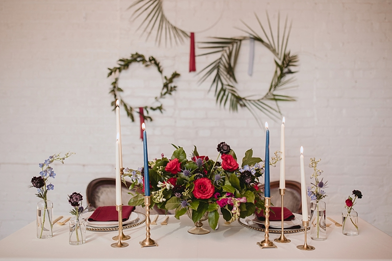 Vintage boho wedding sweetheart table with blue candlesticks and gold metal wreaths with palm leaves