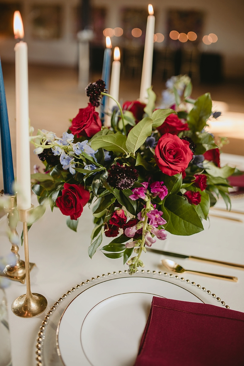Moody fall wedding flower centerpiece with pops of red and blue