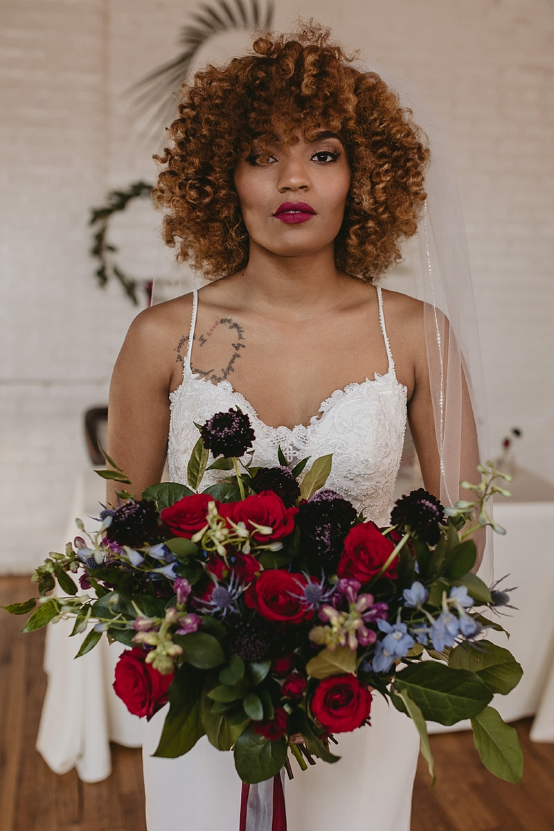 Natural curls and cranberry red lipstick for boho inspired black bride