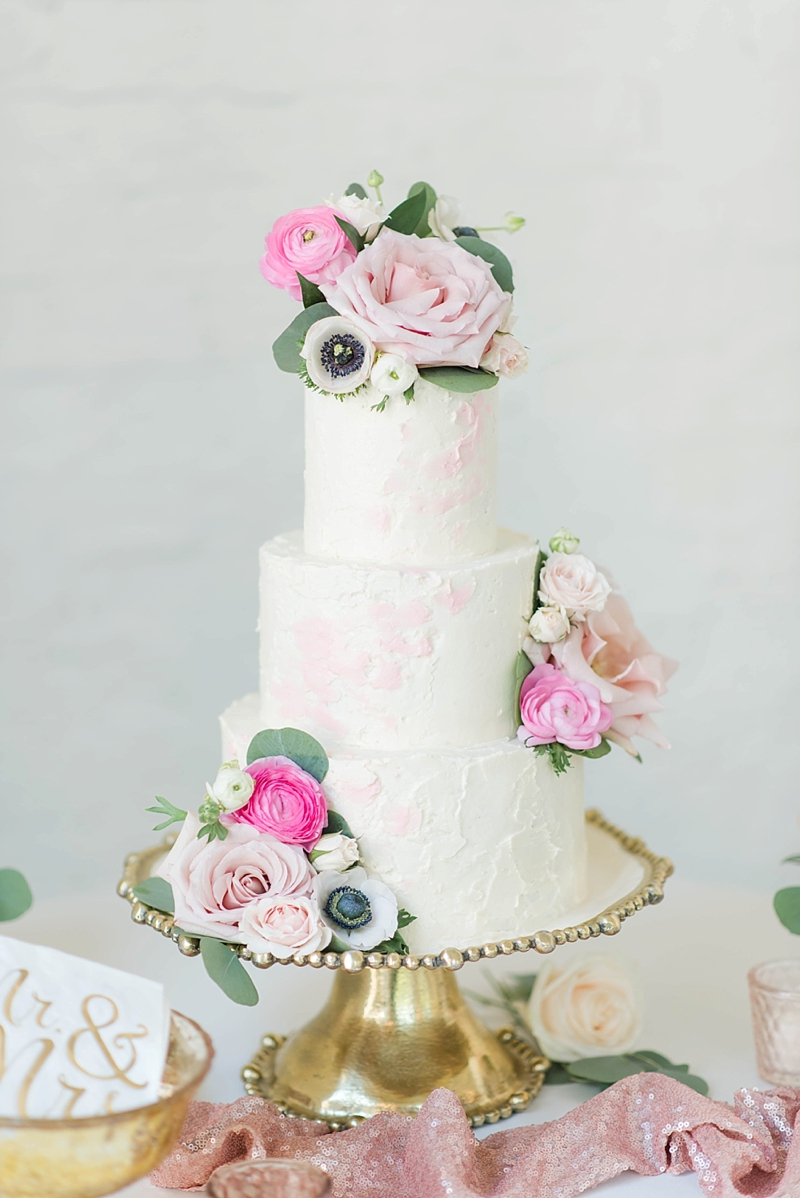 Gorgeous textured pink and white wedding cake with blush flowers on a gold cake stand