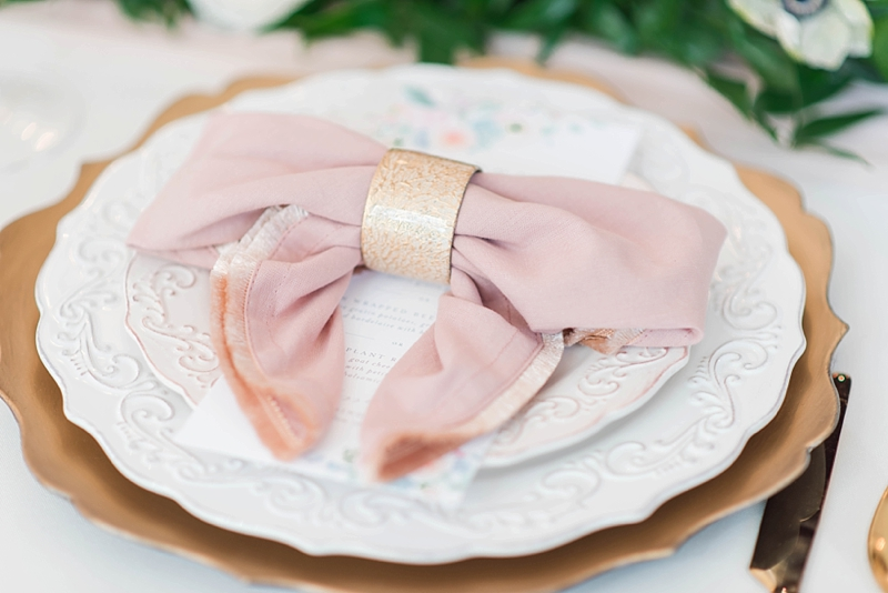 Blush pink napkin folded into a bow for romantic and sweet wedding table setting