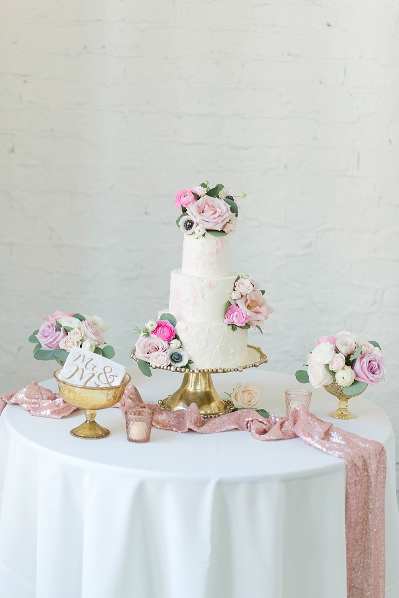 Gorgeous textured pink and white wedding cake with blush flowers on a gold cake stand and pink sequin table runner