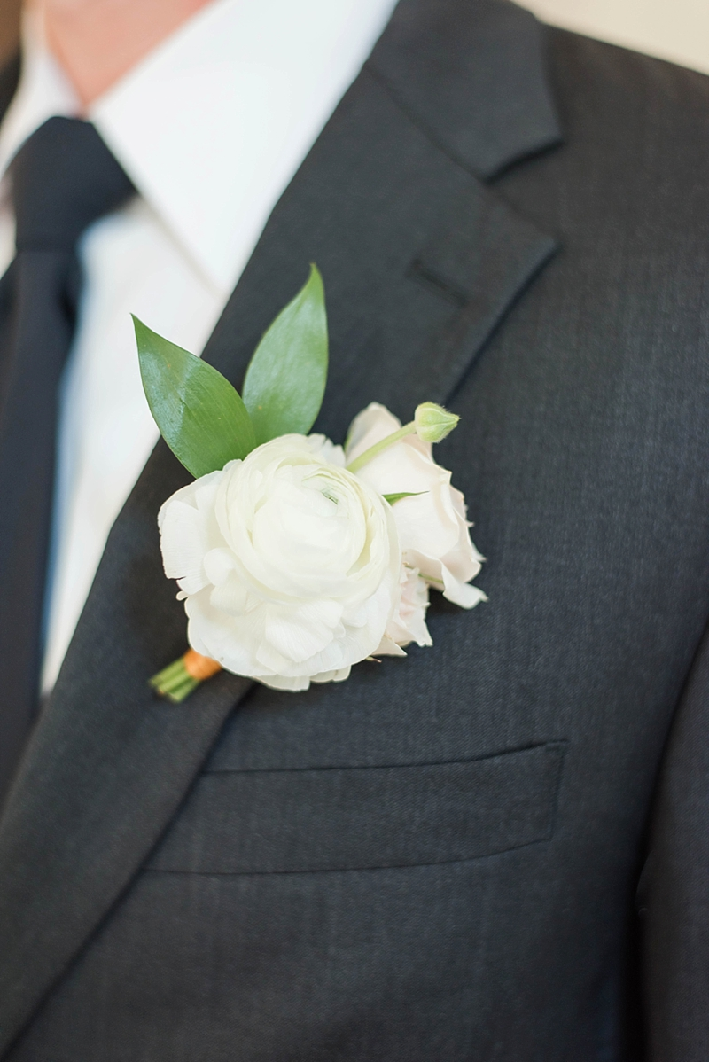 All white flower boutonniere for the groom
