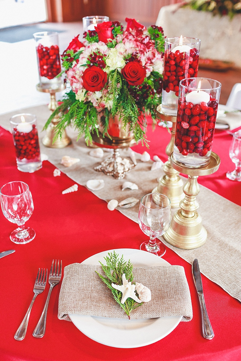 Bright red and green wedding centerpieces with cranberries and starfish for a coastal Christmas wedding