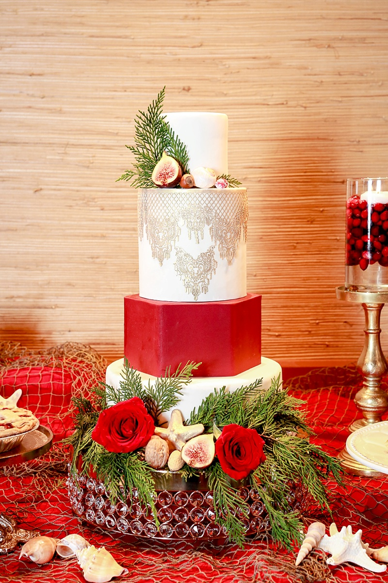 Elegant red and white Christmas wedding cake with gold coastal details like shells and figs
