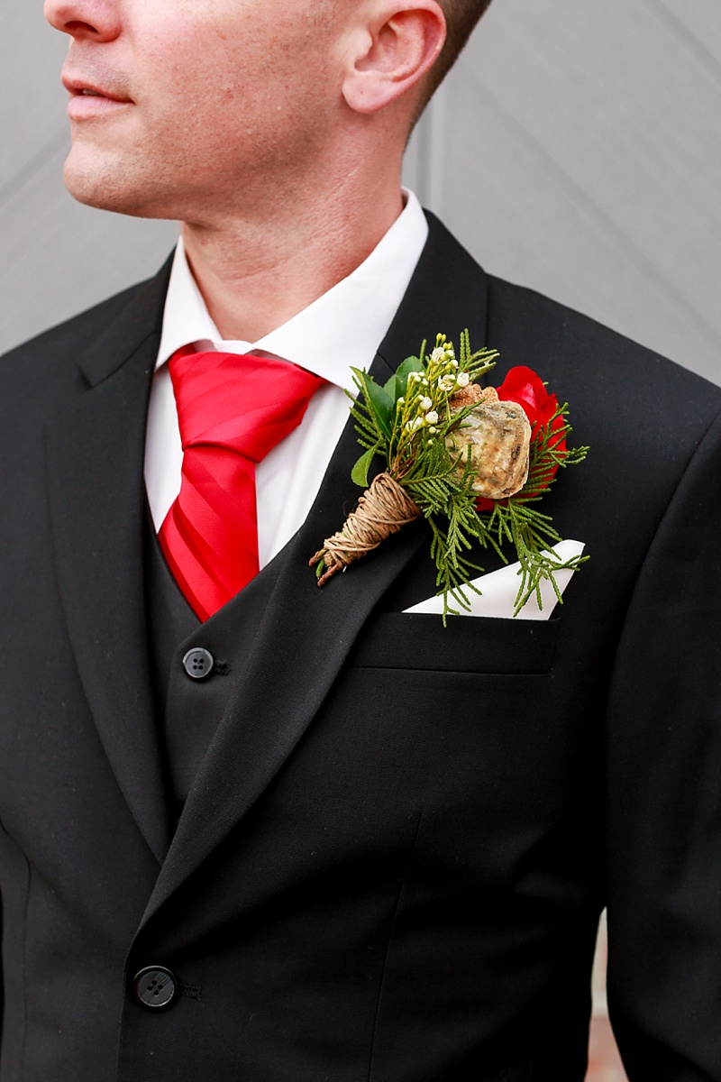 Coastal Christmas inspired boutonniere with mini oyster shell and evergreen