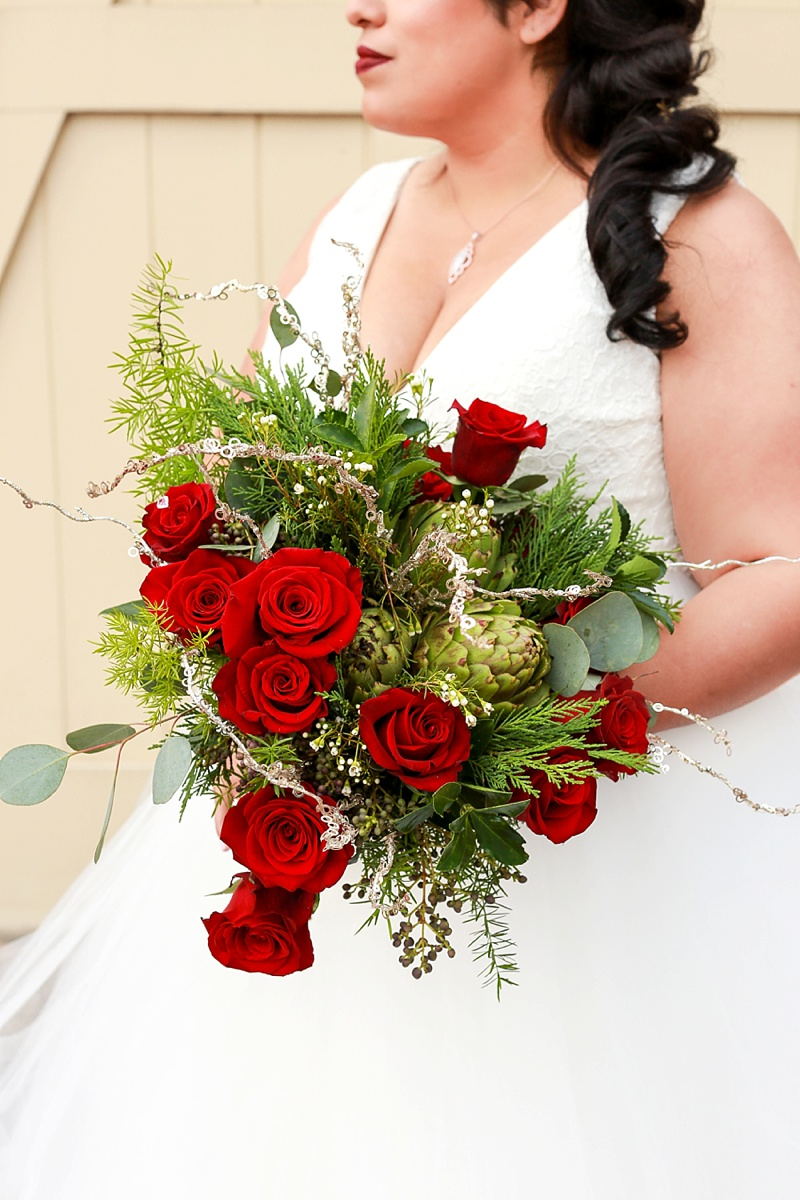 Red and green wedding bouquet with artichokes and roses for coastal Christmas wedding