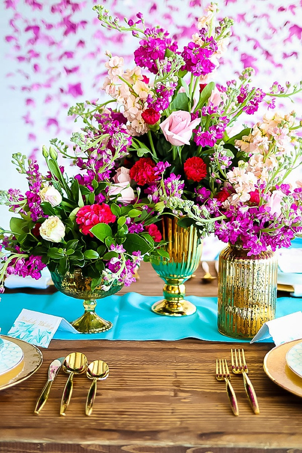 Bright pink and red wedding centerpiece trio in gold mercury vases on a turquoise table runner